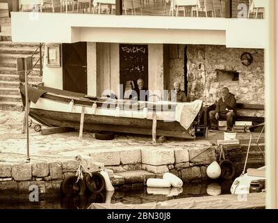 Mediterranean senior male people sitting seated chatting near wooden boat retro look sepia monochrome almost Black and White Lovran Croatia Europe - Stock Photo