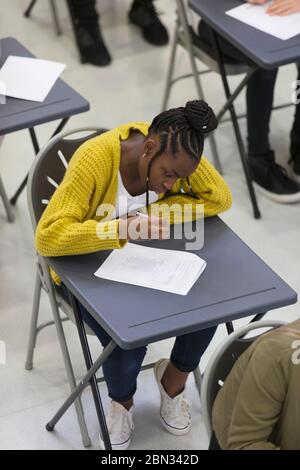 Focused high school girl student taking exam at desk in classroom - Stock Photo