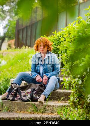 Good-looking ginger hair curly curls redhaired redhair midadult woman outdoors seated with handbag bag in front resting serious eyeshot - Stock Photo