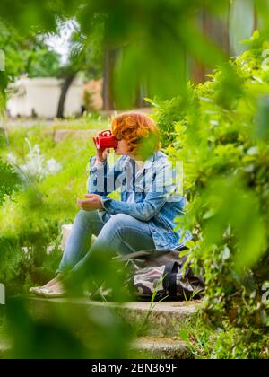 Good-looking ginger hair curly curls redhaired redhair midadult woman outdoors seated with handbag bag and drinking coffee from Red cup refreshment - Stock Photo