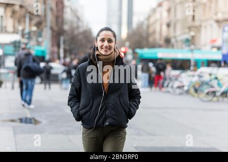Young Indian woman walking on street listening to earphones and smiling at camera.
