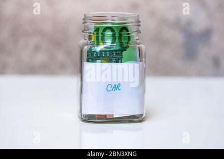 Composition with saving money banknotes in a glass jar with text new car .Concept of investing and keeping money, close up isolated. - Stock Photo