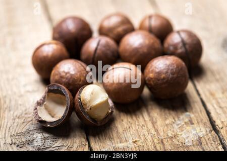 Dried organic Macadamia nuts on wooden table. Studio macro shoot. Black concrete background