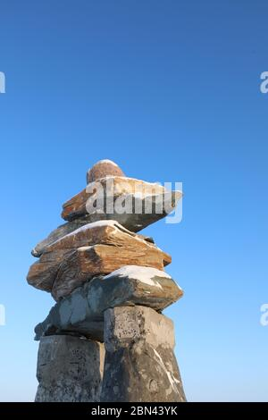 Side profile of an Inuksuk or Inukshuk with blue skies found on the top of a hill in the community of Rankin Inlet, Nunavut, Canada Stock Photo