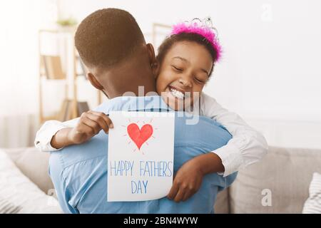 Father's day. Pretty girl giving dad postcard - Stock Photo
