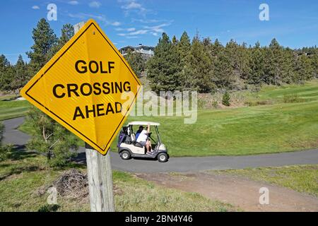 Golfers in a battery powered golf cart go from hole to hole on a golf course in Bend, Oregon. - Stock Photo