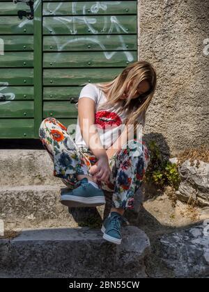 Teengirl tying sneakers awkward posture - Stock Photo