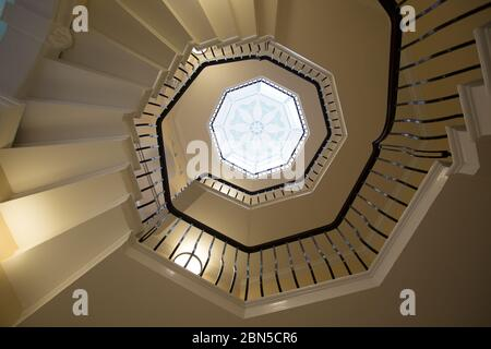 View from the bottom of a spiral staircase looking up to the centre point in the roof of an art deco window, - Stock Photo