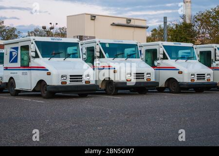 A number parked United States Postal Services vans in front of a Post Office - Stock Photo