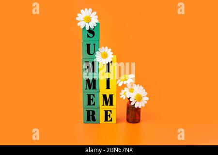 Summer time lettering written on two stacks of green and yellow wooden blocks decorated with chamomile flowers and a small glass bottle with blooming - Stock Photo