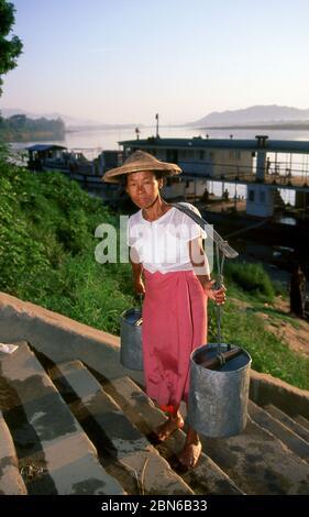 Burma / Myanmar: A woman climbs the steps near the ferry crossing close to Myitkyina's main market, Kachin State (1998).  Myitkyina is the capital cit Stock Photo