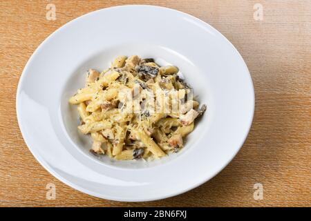 Traditional authentic italian penne al pollo e funghi pasta with mushroom ,chicken and parmesan cheese.
