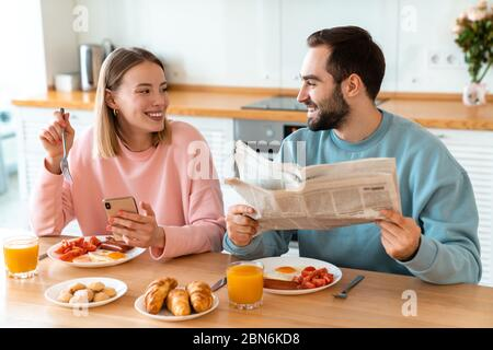 Portrait of young joyful couple using cellphone and reading newspaper while having breakfast in cozy kitchen at home - Stock Photo
