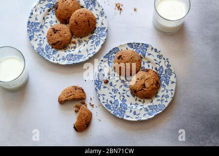 Chocolate chip cookies on blue plates and 2 glasses of milk on a grey kitchen table