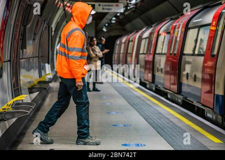 A worker in hi vis orange sits next to an advert for soldier of orange - behind him a womman removes her mask. Passenger numbers remain dramatically down on the tube, even during rush hour and even on teh first day of the easing of government guidance. Those who do travel attempt to obey the guidance on 2m social distancing and possibly around half wear masks - despite isntructions from teh Mayor of London that he expects everyone to wear a mask on public transport. The 'lockdown' continues for the Coronavirus (Covid 19) outbreak in London. - Stock Photo
