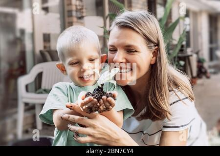 Young plant sprout in little boy's hands. Smiling mother and son. Concept of farming and environment protection. - Stock Photo