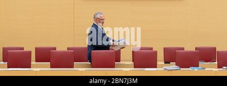 Munich, Germany. 13th May, 2020. Joachim Herrmann (CSU), Minister of the Interior of Bavaria, walks past the chairs during the session of the Bavarian parliament through the empty government bench. Topics of the session on 13.05.2020 include a change in the law on the use of health resort contributions for public transport and the current border controls in the wake of the Corona pandemic. Credit: Peter Kneffel/dpa/Alamy Live News