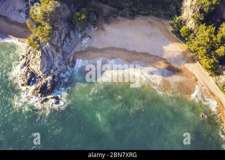 top view of a cove of turquoise waters surrounded with rock cliffs, trees and vegetation, concept of adventure lifestyle and summer holidays in the wi