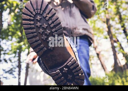 Close up from man in boots walking on forest area - Stock Photo