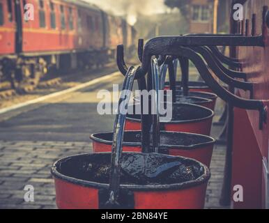 Retro close up of hanging vintage fire buckets on platform of heritage railway station, Severn Valley Railway UK, vintage steam train is leaving.