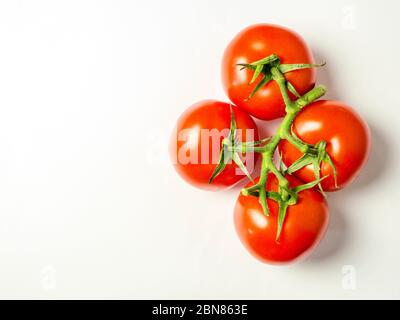 Four ripe red tomatoes on the vine isolated on a white background with copy space - Stock Photo