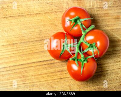 Four ripe red tomatoes on the vine on a wooden chopping board with copy space - Stock Photo