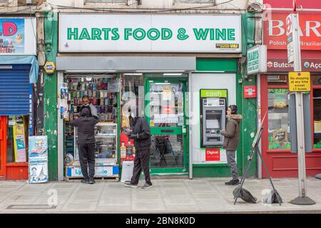 West Norwood, UK. 13th May 2020. People shop at Harts Food & Wine shop in West Norwood during the Coronavirus pandemic in South London, England. (photo by Sam Mellish / Alamy Live News) - Stock Photo