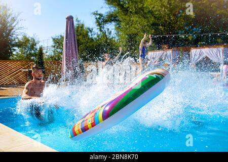Happy friends jumping and splashing in swimming pool with inflatable floats in luxury resort. Young people in swimwear having party in private holiday - Stock Photo