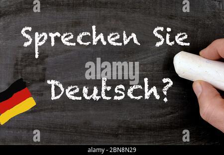 Hand writing sprechen sie deutsch in german, translate do you speak german, on a chalkboard - Stock Photo