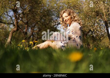 Cute woman rest in the green summer park with dandelions
