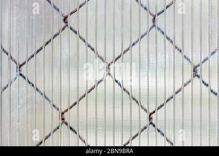 Cells of an iron mesh that shines through the cellular surface of a plastic sheet, to be used as a texture for the background.
