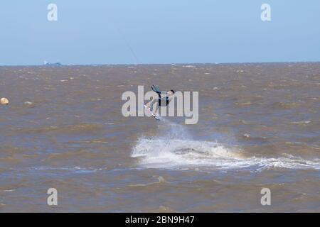 A kite surfer working the wind and surf of the English Channel off the Kent coast, Whitstable - Stock Photo