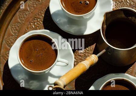 An overhead shot of a Turkish coffee pot with wooden handle and white cups filled with hot black  coffee served on a tray - Stock Photo