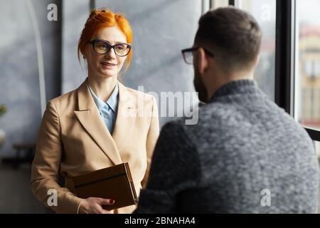 Red haired businesswoman in eyeglasses talking to businessman while they standing at office corridor - Stock Photo