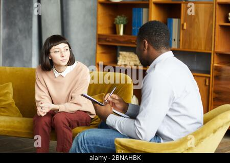 Young woman sitting on sofa and talking to African man while he making notes in document at office - Stock Photo