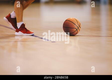 Basketball player walking on wooden court. Basketball over the floor. Basketball sports court - Stock Photo