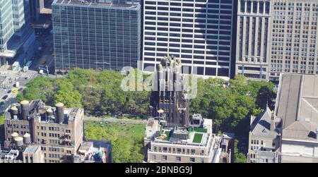 A bird's eye view of the American Radiator Building surrounded by trees under the sunlight at daytime - Stock Photo