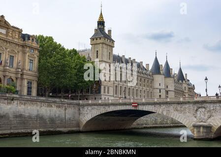 Conciergerie building and watch tower (Tour de l'Horloge du palais de la Cité). Pont au Change bridge on Île de la Cité. Paris, France. - Stock Photo