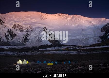 Tent camp at the foot of the snow-covered mountains at night. Hiking. Scenic landscape. Expedition. Lifestyle. Light in tents. - Stock Photo