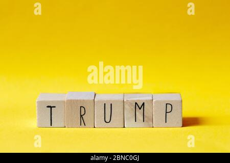 Wooden cubes with the word Trump on orange background, President America concept