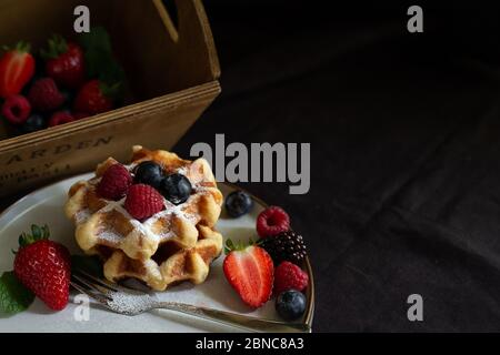 Belgian waffles with strawberries, summer berries on plate on dark old wooden dramatic background. Horizontal view. Menu, banner, poster, mock up. Rustic vintage style of kitchen. - Stock Photo