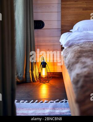Modern interior of cozy bedroom in the hotel with glowing loft lamp on the wooden floor