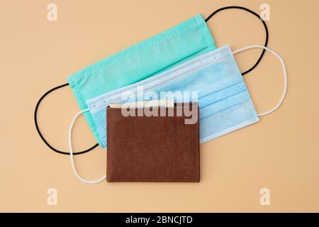 Two disposable medical masks on a yellow background and a wallet. Calculation of the budget during the quarantine period of the crown of the virus, la - Stock Photo