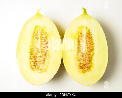Two halves of a canary melon with seeds on a white background - Stock Photo