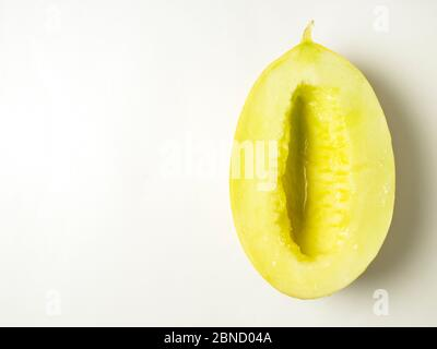 One half of a canary melon without seeds on a white background with copy space - Stock Photo