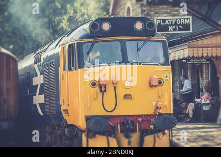 Retro front view close up of vintage UK diesel locomotive leaving train station, Severn Valley heritage railway. Train driver giving thumbs up sign. - Stock Photo