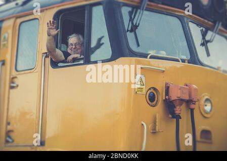 Retro front view close up, British vintage diesel locomotive leaving station, Severn Valley heritage railway, UK. Train driver waving from cab window. - Stock Photo