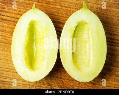 Two halves of a canary melon without seeds on a wooden chopping board - Stock Photo