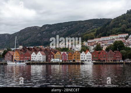 Bergen, Norway - September 09, 2019: Sea water view on historical buildings in Hanseviertel Bryggen wharf in Bergen, Norway. UNESCO World Heritage Sit