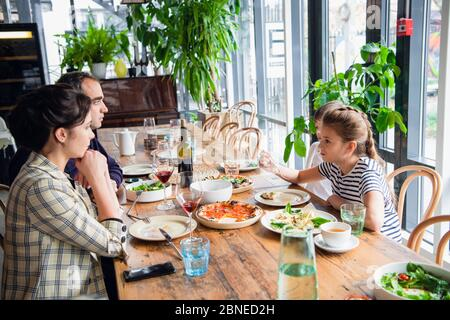 A family of four having a brunch in a cafe on a weekend. - Stock Photo